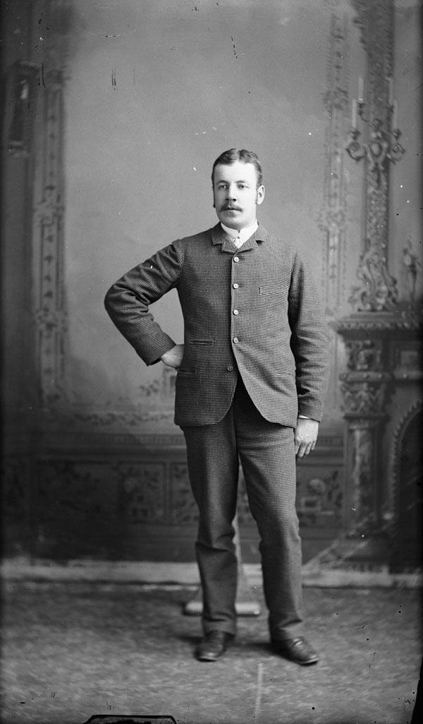 Black-and-white portrait of a man standing in a photo studio.