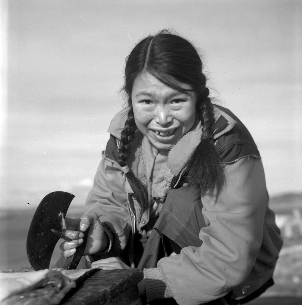 A black-and-white photo of an Inuk woman using an ulu.