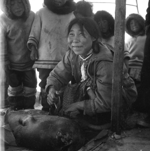 A black-and-white photo of an Inuk woman using her ulu