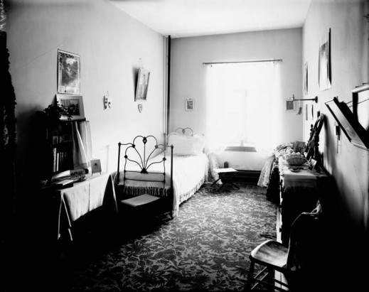A black-and-white photograph of a single bed and furnishings at the Coligny Ladies' College in Ottawa.