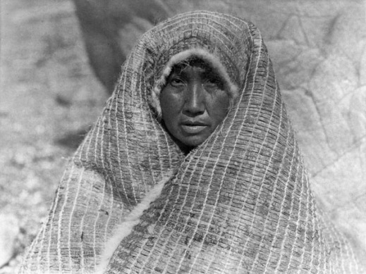 Black-and-white photograph of a woman's face draped by a bark blanket.