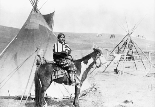 Black-and-white photograph of First Nations woman on horse in front of tepee.