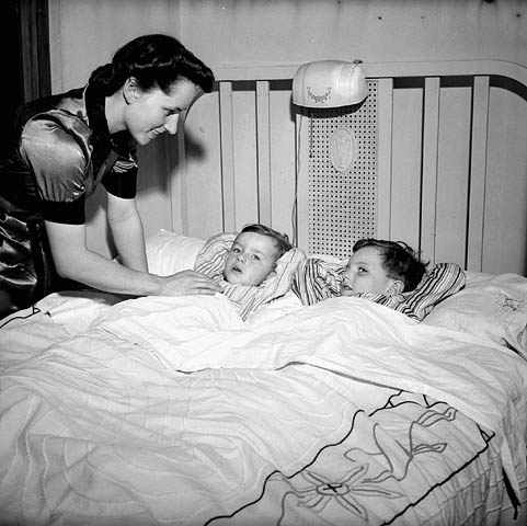 A black-and-white photograph of a mother tucking her two sons into bed.