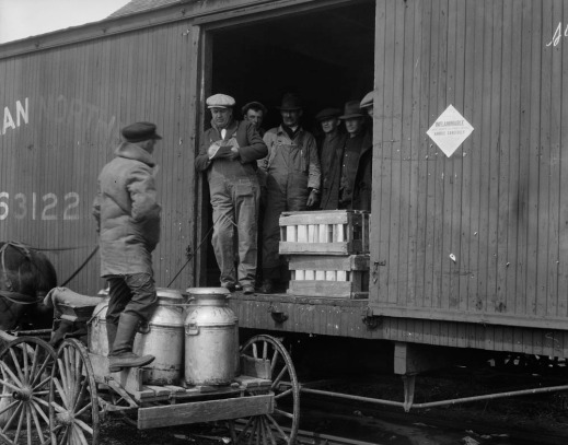 A black-and-white photograph of a farmer delivering large cans of maple syrup by wagon to a train car for shipping. Another man holding a clipboard takes an inventory of the items.