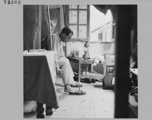 A black-and-white photograph of a man putting his slippers on before getting up from bed.