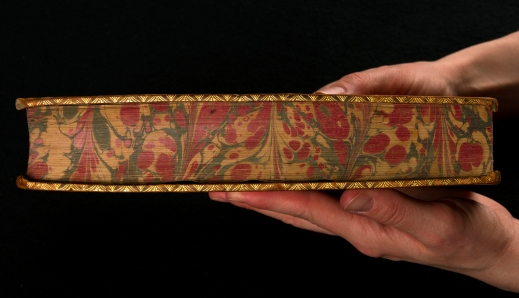 A close-up colour photo of hands holding an elaborately decorated book.
