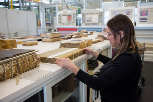 : A colour photo of a person standing at a table in the book conservation lab, repairing the spine of a book.