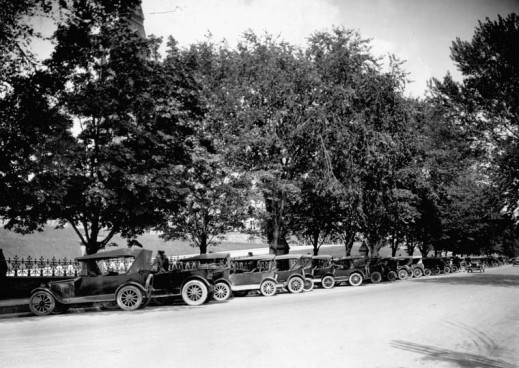 A black-and-white photograph of a tree-lined street with a long row of cars parked at an angle along the curbside.