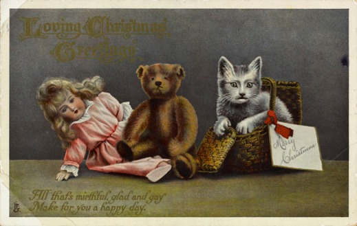 A colour postcard depicting a doll, a stuffed bear, and a cat in a basket.