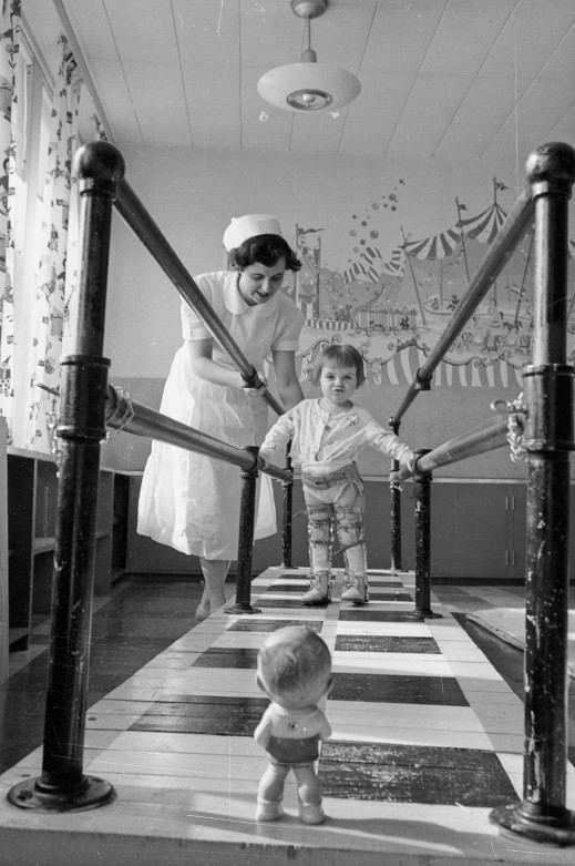 A black-and-white photograph of a woman helping a young child wearing leg braces to walk using parallel bars. A small doll is located at the end of the bars as a focal point for the child.