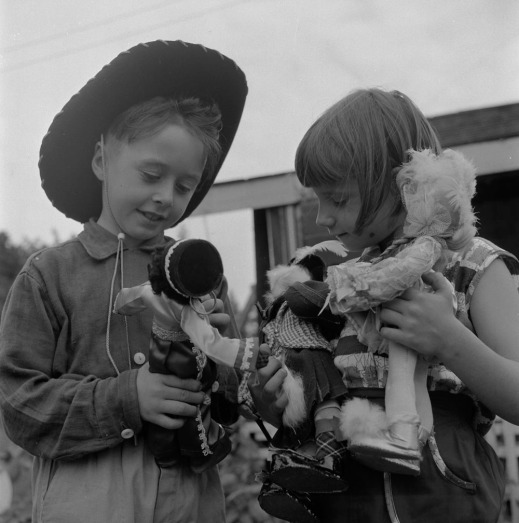 A black-and-white photograph of a boy and a girl holding and examining three dolls.
