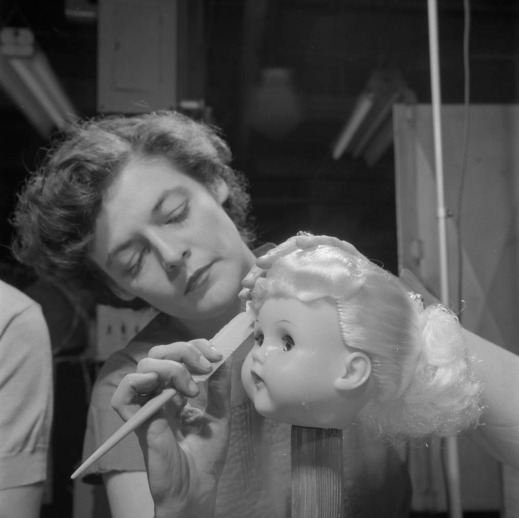 A black-and-white photograph of a woman brushing a doll's hair. The doll's head is mounted on a wooden peg.