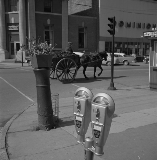 A black-and-white photograph of a double-headed parking meter on a street. In the background there are parked cars and a passing horse-drawn cart.