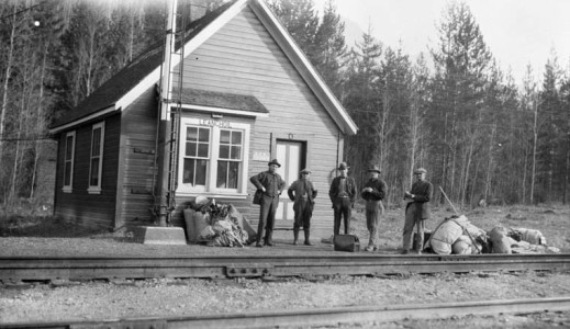 A black-and-white photograph of five men with their baggage, standing outside a small Canadian Pacific Railway station, Leanchoil, British Columbia.