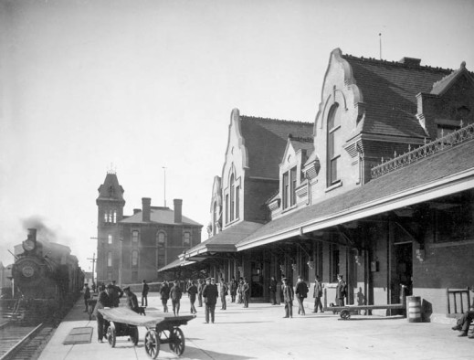 A black-and-white photograph of the exterior of an Intercolonial Railway station. A train is parked to the left, and a group of people stand on the platform, Pictou, Nova Scotia.