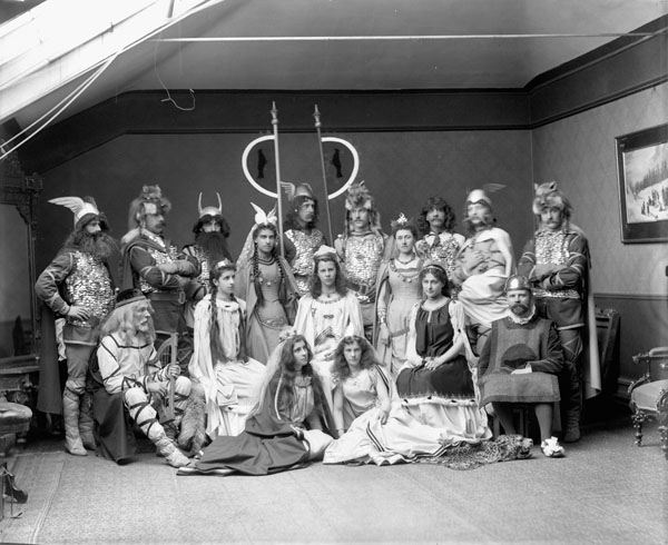 A black-and-white photograph of a group of seventeen men, women and girls wearing Viking costumes in a photography studio.