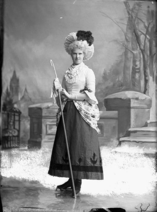 A black-and-white photograph of a woman dressed up in costume as a shepherdess on skates in a photography studio. The backdrop is a painted, snowy scene.