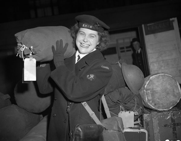A black-and-white photograph of a smiling member of the Women's Royal Canadian Naval Service carrying a large bag on her shoulder.
