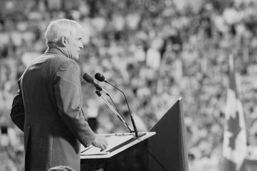 Black-and-white photograph of John Turner speaking into a microphone in front of a crowd. A Canadian flag is visible.