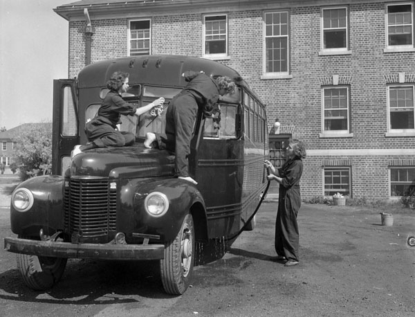 A black-and-white photograph of two members of the Women's Royal Canadian Naval Service washing the front of a bus while their colleague sprays the side of the bus with a hose.