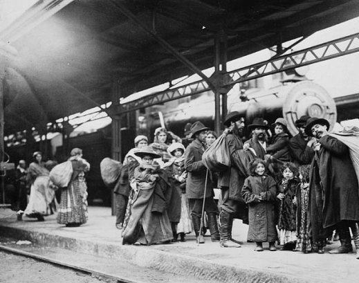 A black-and-white photograph of a group of immigrants on the platform of Union Station, Toronto, Ontario.