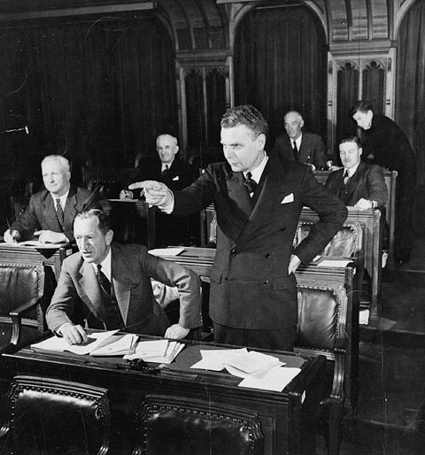 Black-and-white photograph showing MP John Diefenbaker standing and speaking to the House of Commons. Around him, MPs are sitting at their desks.