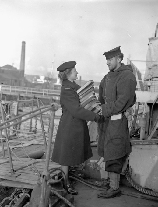 A black-and-white photograph of a member of the Women's Royal Canadian Naval Service handing a man a tall stack of books beside a ship.