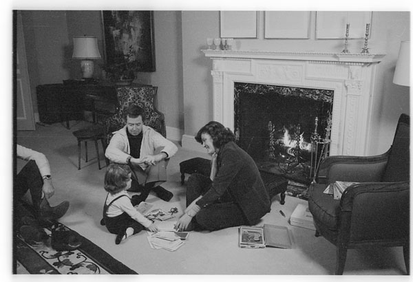 Black-and-white photograph depicting Prime Minister Joe Clark with his wife and daughter, sitting on the floor in the living room, in front of a fireplace.
