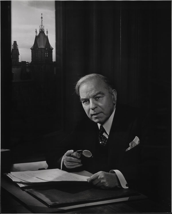 Black-and-white photograph of Prime Minister William Lyon Mackenzie King at his desk. One of the Parliament buildings is visible in the background through a window.