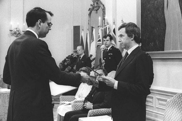 Black-and-white photograph of Joe Clark standing and being sworn in as Prime Minister of Canada. Seated at his side is Governor General Edward Schreyer.