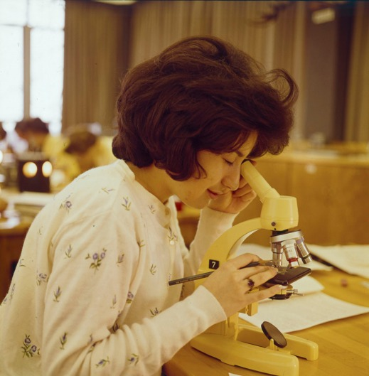 A colour photograph of a woman in a university classroom looking through a microscope.