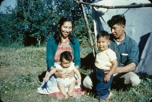 A woman and a man sit in the grass with their two young children in front of a canvas tent.