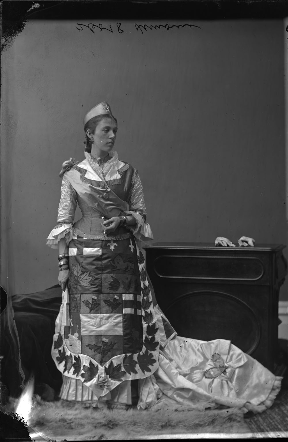 "A black-and-white photograph of a woman dressed up as the ""Dominion of Canada"" in a photography studio. On the front of her dress is the coat of arms of the Dominion surrounded by embroidered maple leaves, with miniature snowshoes on the train of her dress."