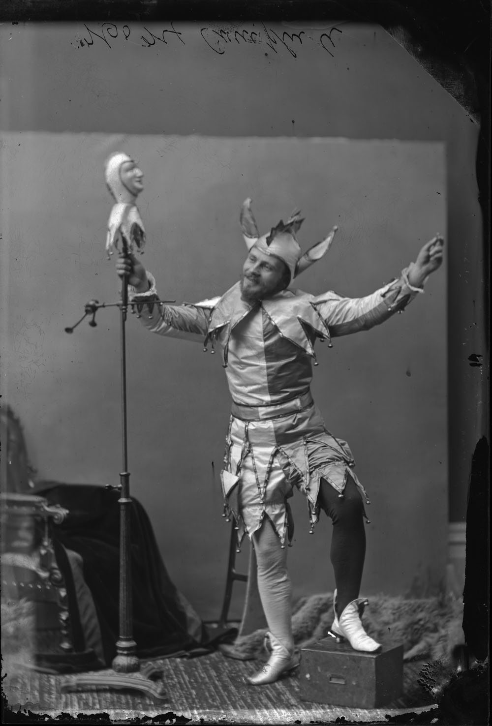 A black-and-white photograph of a man dressed as a jester and posing in a photography studio. He grasps a puppet on a stand in his right hand.