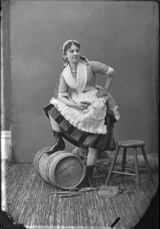 "A black-and-white photograph of a young woman dressed up as a ""fishwife"" and posing in a photography studio. She is shown standing with her left hand resting on her hip, her other hand holding a papier mâché fish and her right foot raised and leaning on a wooden barrel."