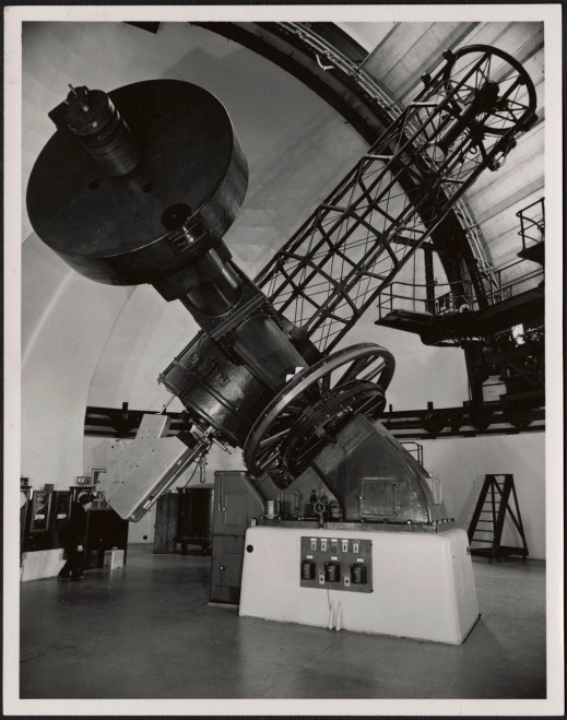 A black-and-white photograph of a man looking into the eyepiece of Victoria's Dominion Astrophysical Observatory Telescope.