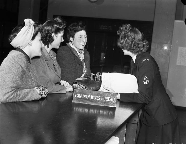 """A black-and-white photograph of a woman in a military uniform leaning across a counter to interview three women beside a sign that reads """"Canadian Wives' Bureau."""""""