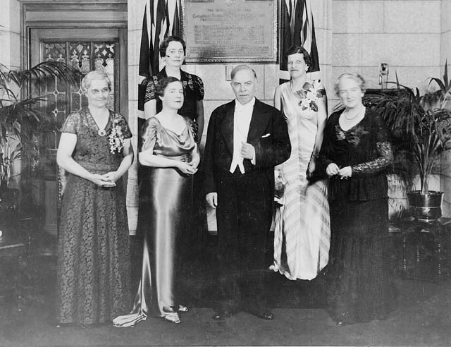 Five women in gowns wearing corsages and one man in a tuxedo standing in front of a plaque.