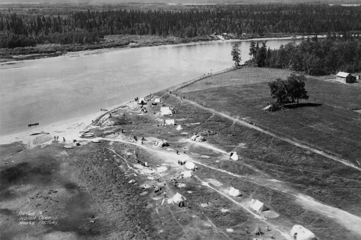 A black-and-white photograph of an aerial view of a riverbank with narrow roads, tents and people walking. On the right are trees and a barn-like building.