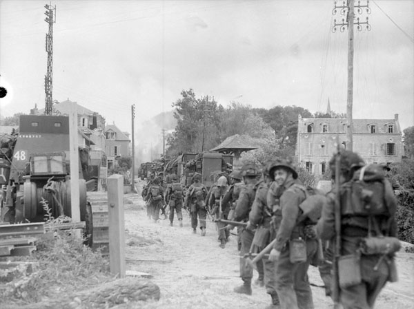 A black-and-white photograph showing a column of soldiers marching up a street in a damaged village.