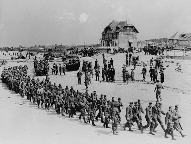 A black-and-white photograph showing a long column of German soldiers being directed by Allied soldiers along a beach, with vehicles, a sea wall, and a prominent house in the background.