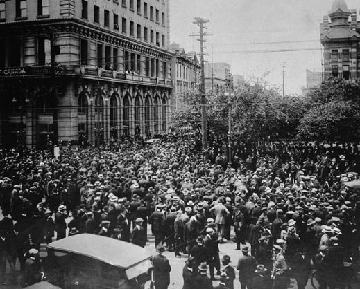 Black-and-white image of strikers filling a street in front of a large building.