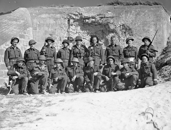 A black-and-white photograph showing two rows of sailors in battle dress, front row crouching, with a damaged fortified concrete structure behind them.