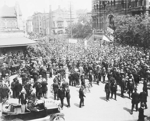 Black-and-white image of strikers in a crowded city street holding signs.