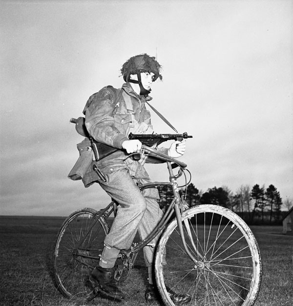 A black-and-white photograph showing a soldier in a paratrooper jump smock, holding a Sten sub-machine gun, sitting on a bicycle in a field.