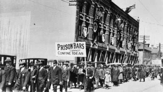 "Black-and-white image of protestors in a street, with a sign reading ""Prison bars cannot confine ideas."""