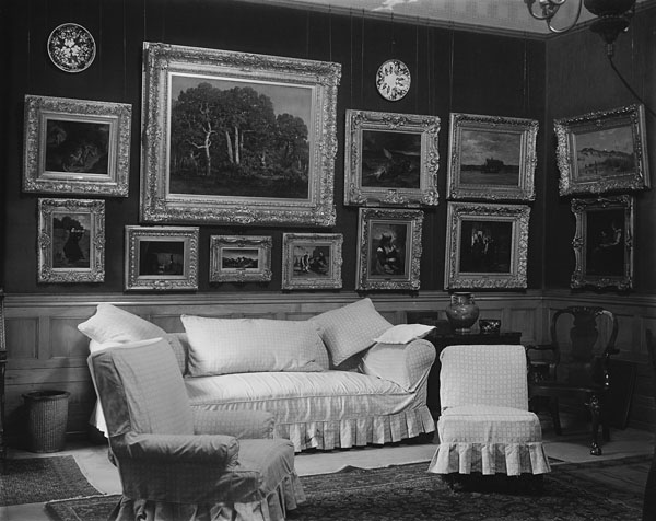 A black-and-white photograph of a living room furnished with plush chairs, paintings and a couch.