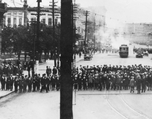 Black-and-white image of a streetcar with smoke rising from it, with onlookers in the foreground.
