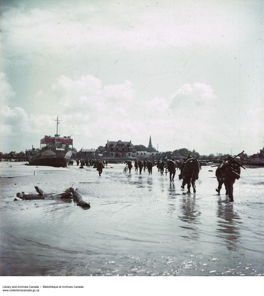 A colour photograph showing soldiers, laden with arms and equipment, walking in shallow water towards a French village.