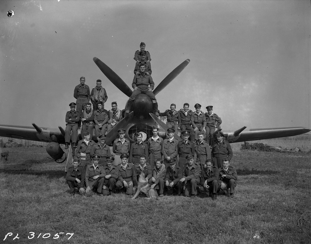 A black-and-white photograph showing a group of RCAF personnel posing beside and on top of a fighter-bomber aircraft, fitted with a large bomb.